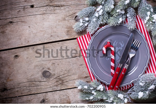 Grey  plate, knife and fork, napkin and  decorative candy cane on rustic wooden background. Top view. Place for text. Selective focus