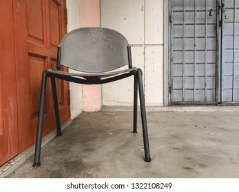 Grey Polyvinyl Chloride (PVC) chair left outside the exterior building in front the wooden door.