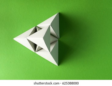 grey pyramid made from tetrahedron geometry models on green background