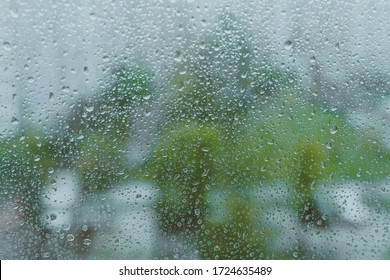 grey rainy droplets on a window glass. transparent surface. drops on window shield in a rainy days  in a city. stormy weather.  rainy season. stormy weather. isolation sad depression concept.