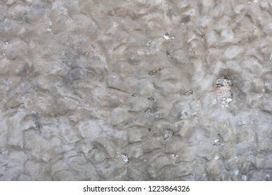 Grey rendered lumpy stone wall with small cracks and white flecks