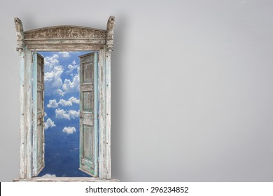 Grey retro style wooden door opening and view of sky and cloud