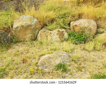 grey rocks or boulders and green and yellow grasses