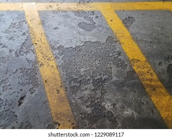 grey, rough, and worn cement or ground with yellow lines