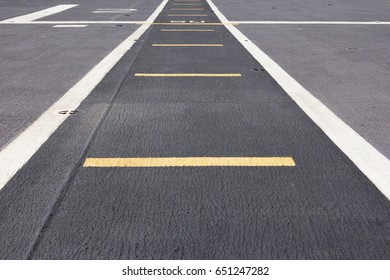 Grey runway path with white stripes on top deck of ship.