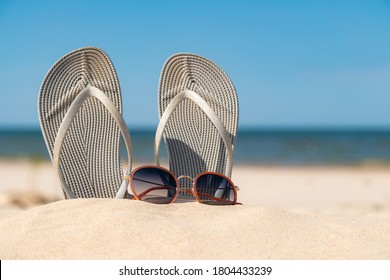 Grey sandals at the beach on a beautiful sunny day. Slippers in the sand by the sea. Flip flops at the shore by the ocean.