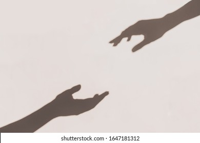 Grey shadows of hands reaching each other on the wall. Abstract blurred effect with space for text.
