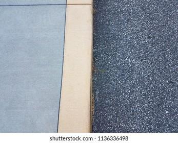grey sidewalk, cement curb, and black asphalt