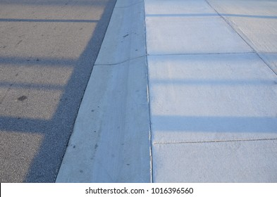 grey sidewalk and sloped curb onto the street