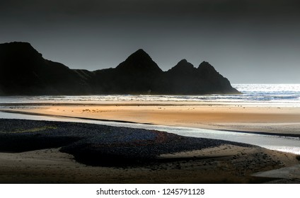 Grey skies at the monolithic outline of Three Cliffs Bay on the Gower peninsula, Swansea, South Wales, UK