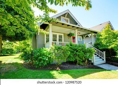Grey small house with porch and white railings with summer landscape.