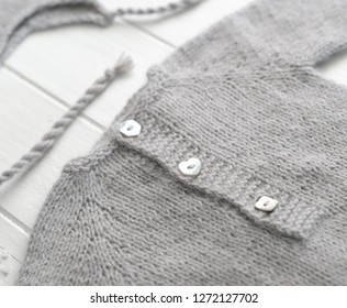 Grey small knitted clothes for babies composed on the white table