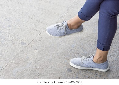 grey sneakers on asian female feet., with copy space for text. fashion concept. waiting concept.