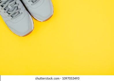 Grey sneakers on yellow background. Concept of healthy lifestile and food, everyday training and force of will. Color of the year 2018.