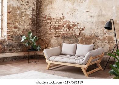 Grey sofa between plant and black lamp in wabi sabi loft interior with red brick wall. Real photo