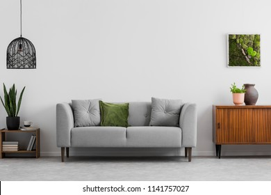 Grey sofa with pillows next to wooden cupboard in living room interior with lamp and poster. Real photo