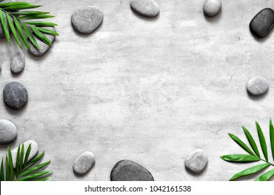 Grey spa background, spa concept, palm leaves and grey stones, top view