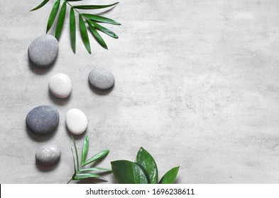 Grey spa background, spa concept, palm leaves and grey stones, top view.