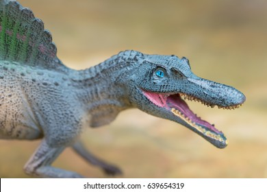 grey spinosaurus toy standing on rock close up