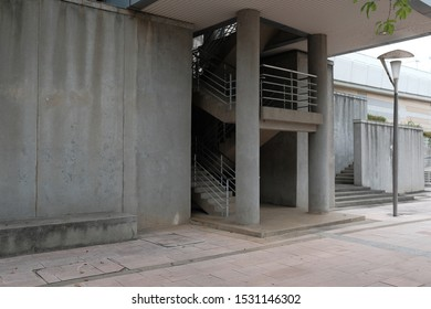 Grey stairwell in between a concrete wall and a lamp post