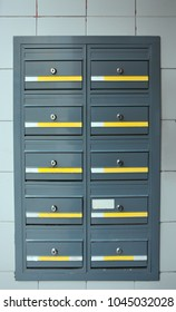 grey steel modern lockable mailboxes in a tiled exterior wall with yellow and white labels
