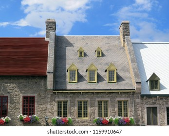 Grey stone houses with window flowers close to each other wall to wall