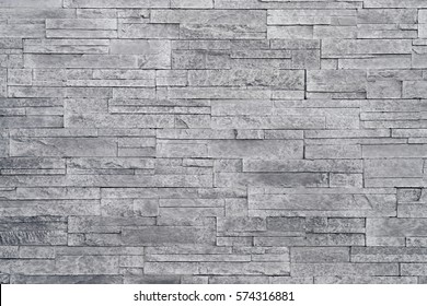 Grey stone wall background. Stacked stone tiles are often used in interior design decors as accent wall. Use this gray texture in graphic design to create a wallpaper, background, backdrop and more!