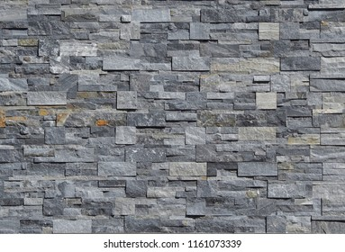 Grey stone wall cladding made of strips and square blocks stacked . Background and texture.