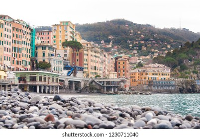 Grey stones on the beach of Camogli and typical colorful houses