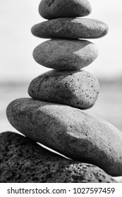 Grey Stones Or Pebbles Stacked In Pyramid Art Form Outdoors On Sunny Day Blurred Background