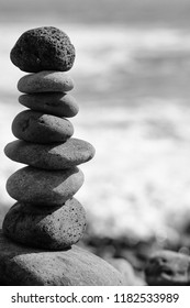 Grey stones or pebbles stacked in pyramid art form outdoors on sunny day on blurred background. Harmony and balance