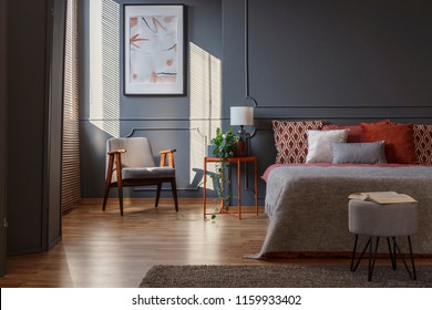 Grey stool in front of bed in dark bedroom interior with armchair against the wall with poster