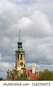 Grey storm clouds are gathering above a church steeple. The copper dome is green with age, while the church is cream and gold, with a red roof.