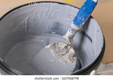 Grey stuck plaster in a bucket with trowle