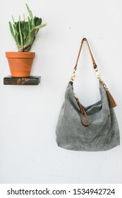 Grey suede leather bag hanging on wall next to cactus, styled, copy space