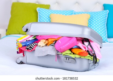 Grey suitcase with clothing on bed close-up