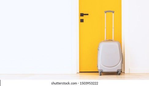Grey suitcase near the door in the hallway