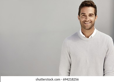 Grey sweater guy smiling against grey background
