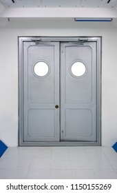 Grey swing doors with circlie windows and automatic hydraulic leaver hinge door against white wall.