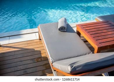 Grey Towel on relaxing pool bed beside swimming pool.