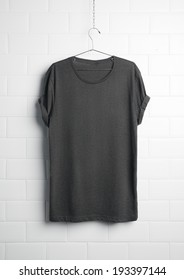 Grey t-shirt hanging on white wall
