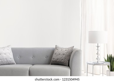 Grey velvet pillows on elegant sofa in bright new york style living room, real photo with copy space on the empty white wall