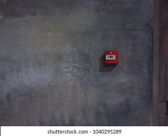 Grey wall and fire button. Dark abstract background with the wall.