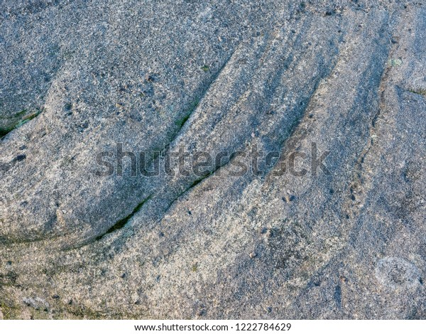 Grey, weathered rock with ridges and swirls. Moss and lichen growing in the cracks and crevices. Close up.