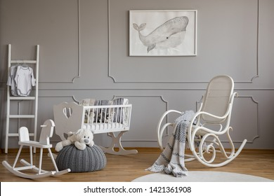 Grey whale on poster in classy baby room interior with white wooden rocking chair, rocking horse, crib and scandinavian ladder, copy space on empty wall