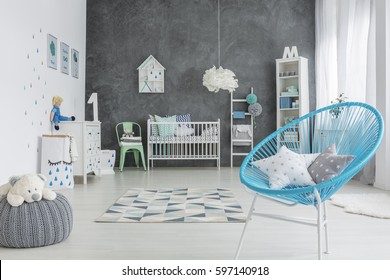 Grey and white baby room with round chair and cot