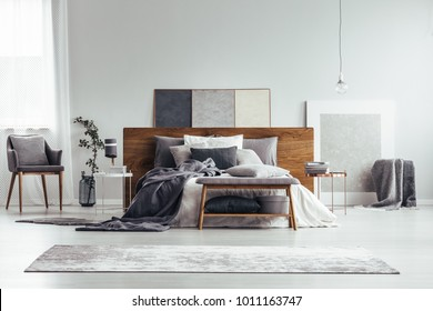Grey and white bedroom interior with armchair, carpet, bed and painting standing on the floor