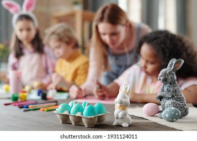 Grey and white toy rabbits and group of painted Easter eggs in egg-box standing on wooden table with kids drawing pictures on background