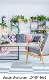 grey wooden armchair on striped rug next to sofa with patterned colorful pillows in living room