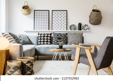 Grey wooden armchair in scandi living room interior with patterned posters above settee. Real photo